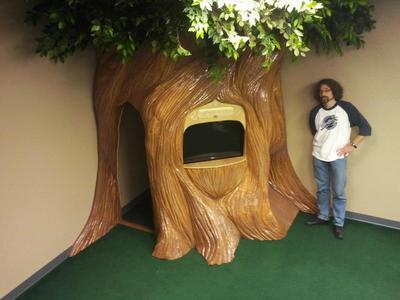 This a preschool space we created featuring a tree playhouse with an interchangeable TV and puppet theater.