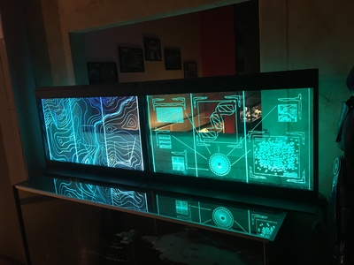 These are laser etched, RGB LED illuminated displays. We created and installed several at the Scum and Villainy bar. Others were created for a sci-fi laboratory set dressing and are available for rent.
