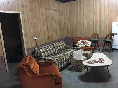 This a pop-up set of a 1970's style basement living room space with wood paneling and brick foundation.